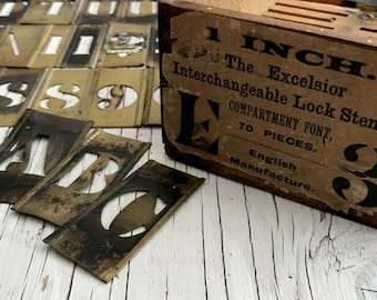 A box of a near complete set of The Excelsior Lock Stencil Brass plates: letters, numbers and punctuation, 69 stencils.