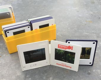 3 vintage 35mm Kodak slide containers with 64 slides included, various sightseeing themed slides. Photography ephemera.
