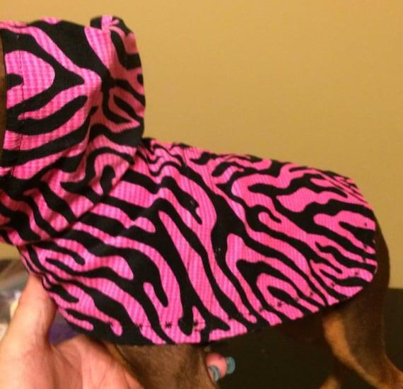 MANTEAU petit chien de rayures de tigre noir sur gaufre rose vif tissus léger. À capuche. Se glisse dessus de la tête et Velcros sous le ventre.