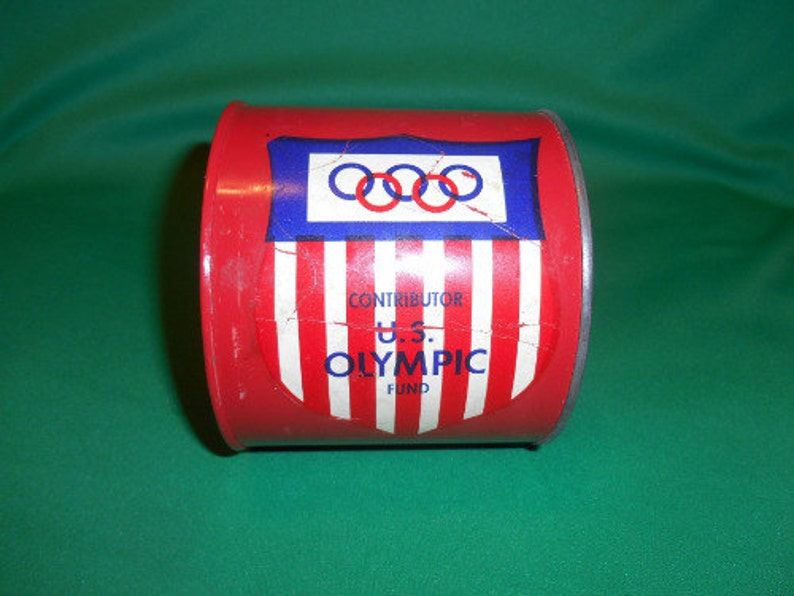 1 Circa 1960/'s. One US Olympic Fund Bank Pressed Steel
