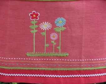 Cheerful Spring flowers on a pink cotton apron