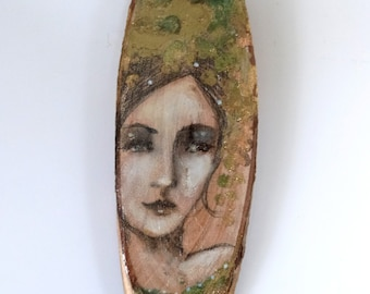 Portrait on oval log, woman in oxidized gold. Cybele Gold.