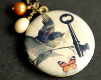 Key Bird Butterfly Locket Necklace. Bird Necklace with Beige Teardrop and Orange Fresh Water Pearl Charm. Orange Butterfly Necklace.