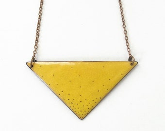 small yellow triangle made of enamel with dots painted on copper chain
