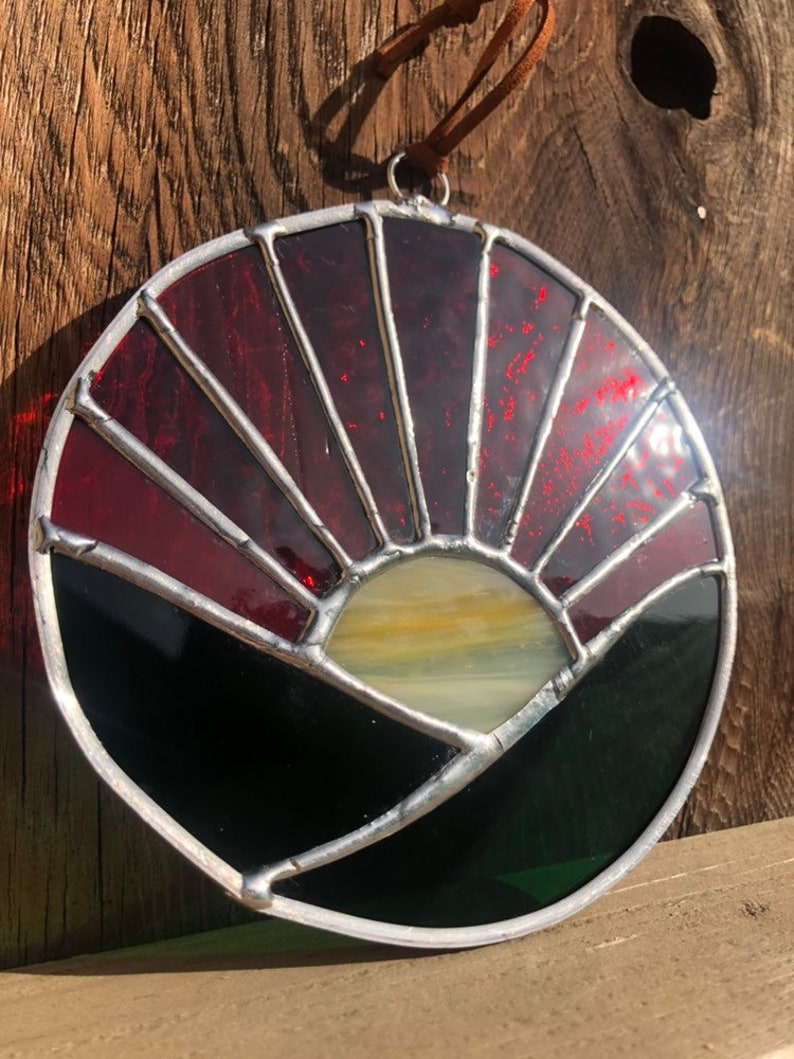 Stained Glass Round Sunrise Suncatcher in Varying Reds Oranges Yellow and Green