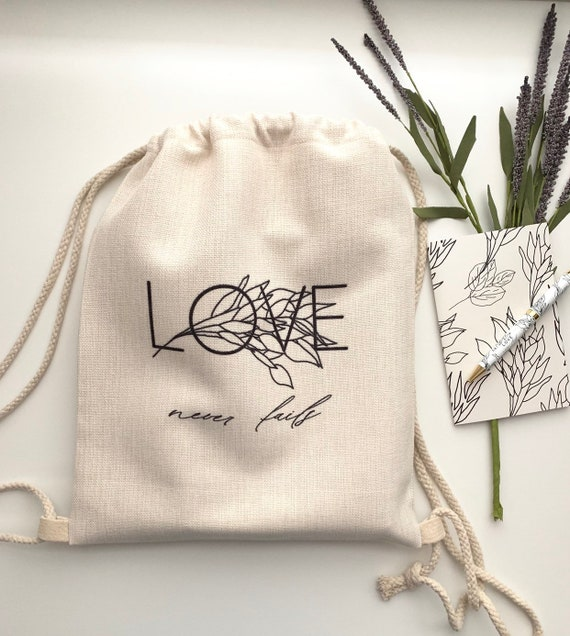 Love Never Fails Drawstring Linen Canvas Tote -Black print