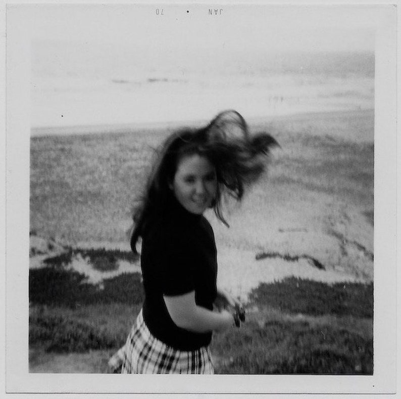 Old Photo Teen Girl wearing Black Turtleneck and Plaid Skirt Hair Blowing at the Beach Soft Focus 1970s Photograph Snapshot Vintage