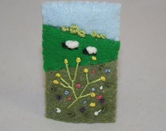 Embroidered Felt Summer Brooch - Hill-side sheep, meadwo flowers and distant trees stitched by Lynwoodcrafts