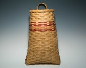 Hand woven pocket basket with peach accents