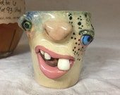 SHOT GLASS - wheel thrown, hand altered and sculpted. A friendly face to enjoy your favorite beverage. Holds 1 oz of your favorite beverage.