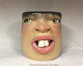 GLASS/NEEDLEHOLDER, wheel thrown, hand altered and sculpted. A friendly face to enjoy a beverage or hold odds and ends.