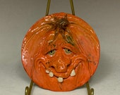 PUMPKIN SAUCER Wheel thrown, hand altered and sculpted ceramic saucer or wall hanging. A friendly face to enjoy for the holiday season.