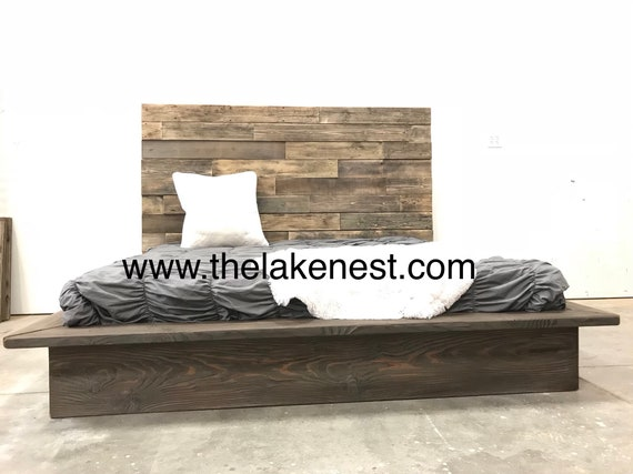 Natural browns textured driftwood finished platform bed with horizontal staggered patched recycled reclaimed wood headboard