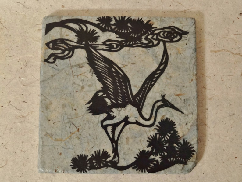 Trivet: Paper-covered stone with hand-cut crane design image 0