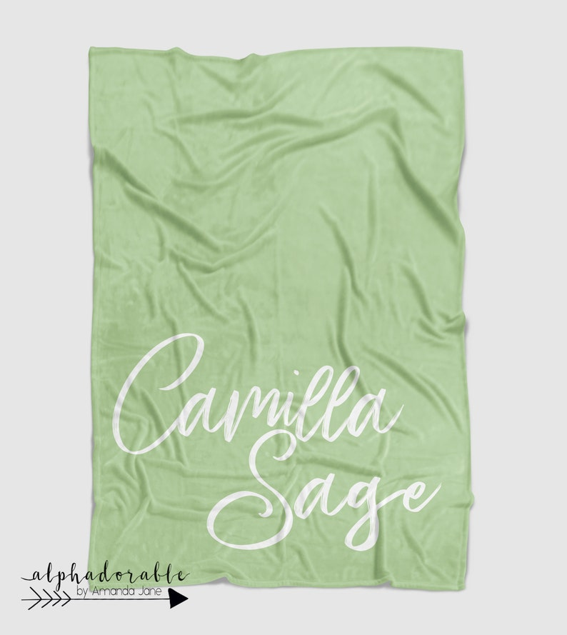 Personalized buttery soft minky baby blanket in light sage green with white name monogram.