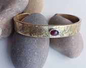 Word jumble golden brass cuff bracelet with a silver set red garnet cabochon, vintage style bangle with stamped texture and gemstone