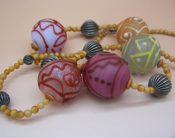 Handmade lampwork necklace of 5 large blown hollow glass beads with line designs, translucent pink, purple, gold, etched, 25 inches