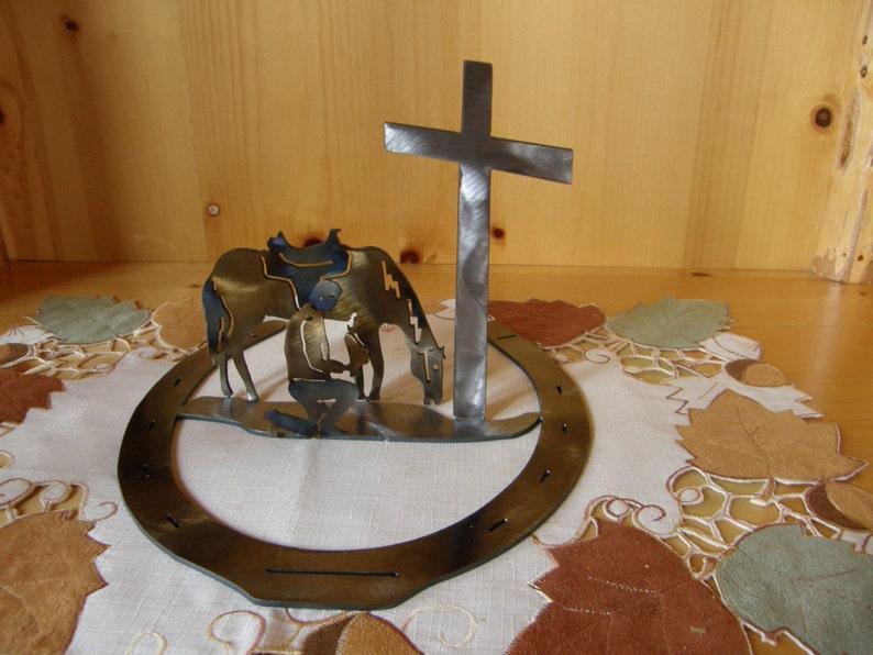 Metal sculpture of praying cowboy with horseshoe base image 0