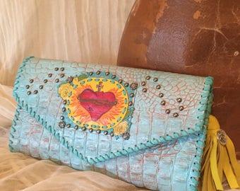 Aqua alligator-look leather clutch, yellow tassel, sacred heart and roses design