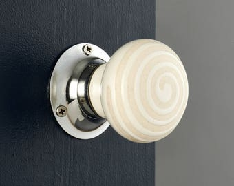 P142 - A pair beige cream swirl ceramic mortice door knobs