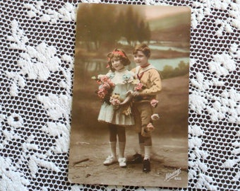 Antique Sepia with Color Photo Postcard 1900s Young Children Cute Boy & Girl covered in Roses Standing Outdoors by a River Vintage Post Card