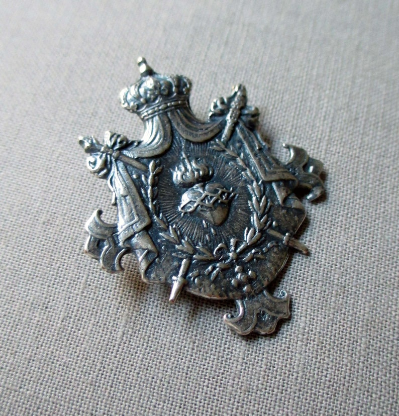 silver plated shield charm or pendant medal with crown sacred heart and swords jewelry finding