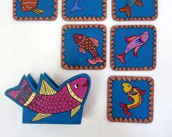 6 coasters with fish designs with blue and multicolored storage box