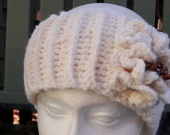 Crochet cream headband with flower detail and brown beads on the side