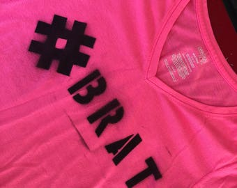 Stencil spray paint tag #BRAT on neon pink long sleeve v-neck t-shirt