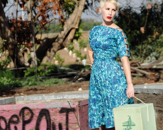 Alluring late 1950s day dress in novelty print florals and open work shoulder design.