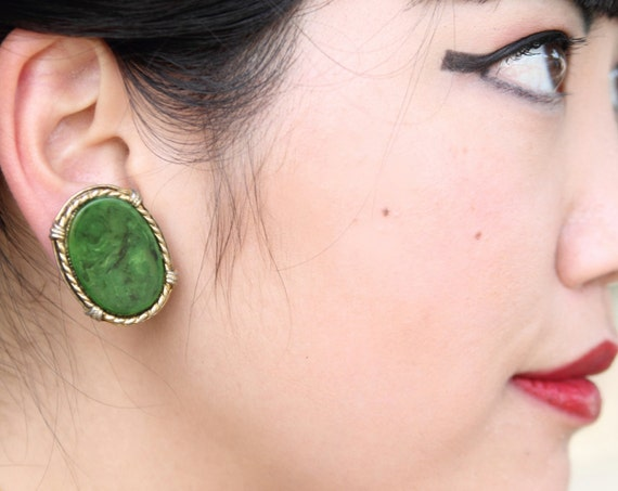 """Green swirl, end of day, oval bakelite earrings with goldtone frame, clip ons, 1"""" x 1 1/4"""""""
