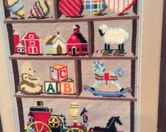 Vintage needlepoint picture of a toy shelf