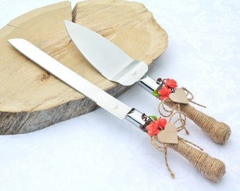 Rustic wedding cake server set decorated with wooden heart coral flowers and wrapped in twine
