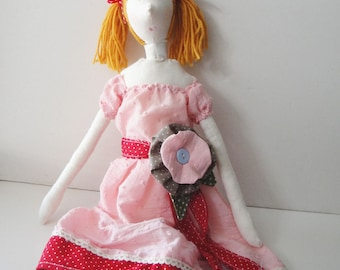 Blonde stuffed fabric doll with a big flower on her pink dress