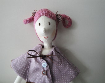 Stuffed fabric doll with pink ponytails and purple clothes