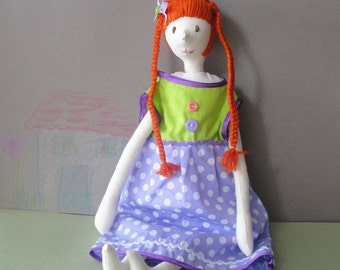 Rag handmade stuffed doll with orange hair wearing a purple green dress for children