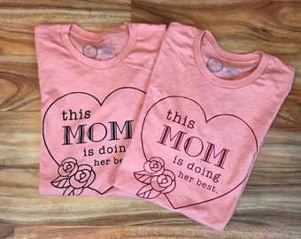This Mom is Doing Her Best on Heather Pink Prism softspun unisex shirt. Black of maroon ink.