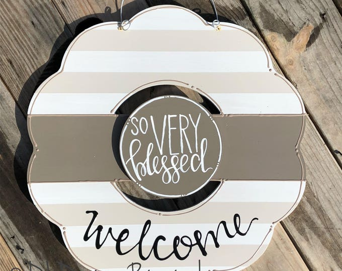 neutral wreath door hanger with stripes and hand lettering