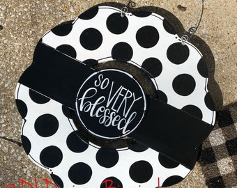 Black and white wreath door hanger with polka dots and hand lettering