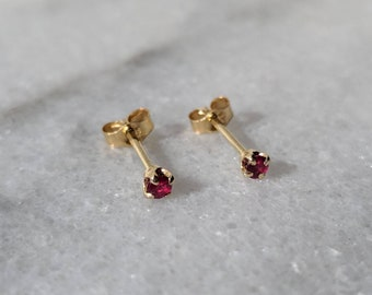 Sweet 14k gold 2mm petite red ruby stud earrings.