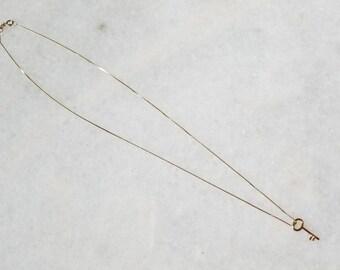 Tiny 14k gold lucky key pendant