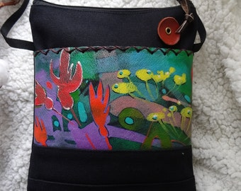 A unique leather handmade purse/bag with a flower painting .