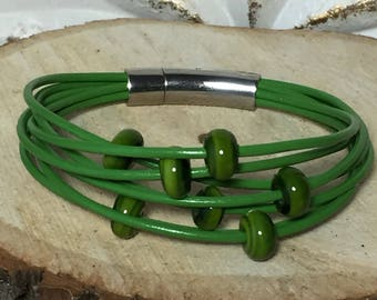 Dark lime green multistrand leather bracelet with handmade tone on tone lampwork beads and a stainless steel push-in locking clasp