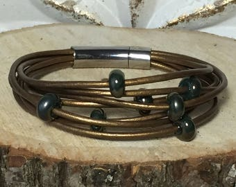 Metallic bronze multistrand leather bracelet with handmade tone on tone lampwork beads and a stainless steel push-in locking clasp