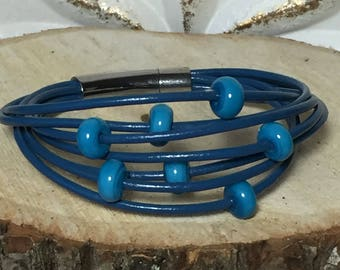 Blue multistrand leather bracelet with handmade tone on tone lampwork beads and a stainless steel push-in locking clasp