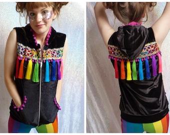 Velvet fleece lined sleeveless hoodie with a rainbow of tassels,rainbow braiding and pom pom trim.