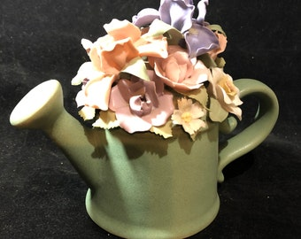 Pottery watering can with porcelain flowers music box.