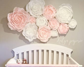 Blush nursery wall paper flowers. Paper flower wall display. Shop window crepe paper flowers. White and pink garden party decor.