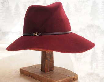 Elle: Cross front tribly crown with floppy soft brim of burgundy velour fur felt with matching leather trim and antique brass finding
