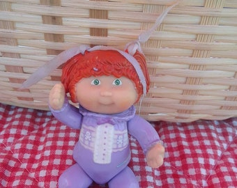 Vintage cabbage patch poseable doll in purple outfit.
